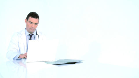 Doctor examining x-ray image and writing on his laptop Footage