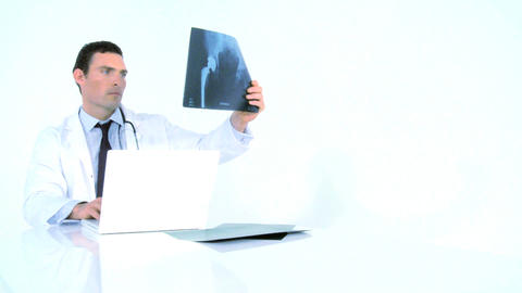 Doctor examining x-ray image and writing on his laptop Stock Video Footage