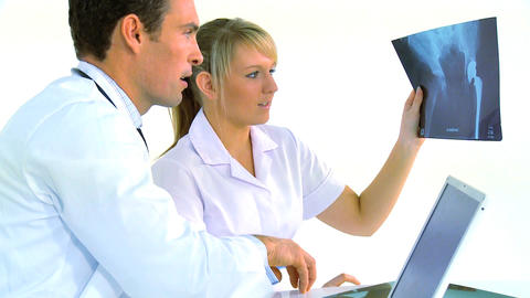 Healthcare workers at desk with x-ray image, motion jib Stock Video Footage