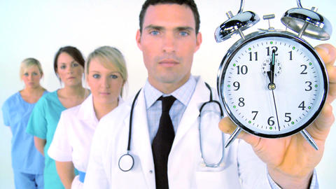 Medical team - doctor holding alarm clock showing a few seconds after midnight Footage
