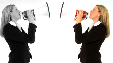 Female twins shouting at each other with megaphone isolated on white Footage