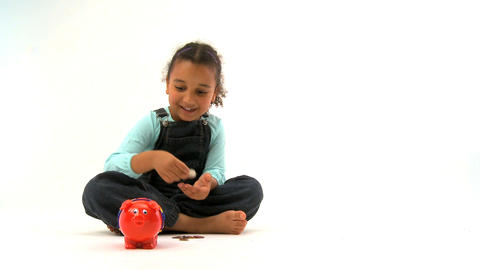 Little girl insert coins into a piggy bank Stock Video Footage
