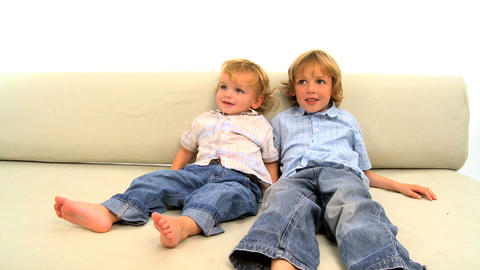 Two little boys lying on the sofa on white background Stock Video Footage