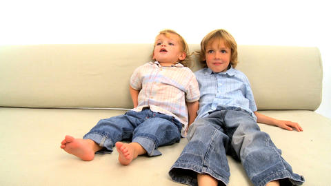 Two little boys lying on the sofa on white background Footage