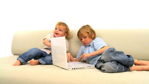 Two little boys playing with laptop on the sofa Stock Video Footage
