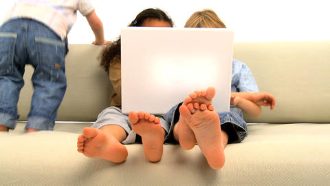 Two little boys and girl sitting on the sofa and enjoying... Stock Video Footage