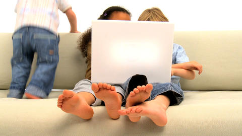 Two little boys and girl sitting on the sofa and enjoying themselves Footage