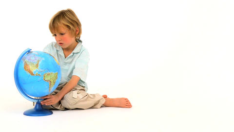 Little boy looking at a globe isolated on white Footage