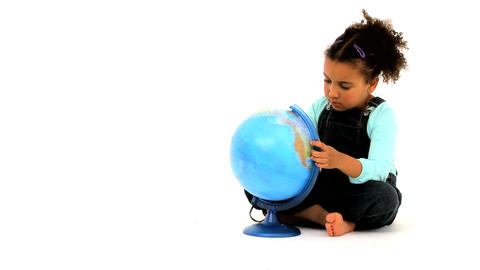 Cute african american girl looking at a globe on white background Footage