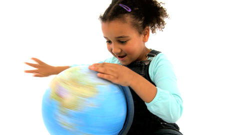 An adorable african american girl playing with a globe isolated on white Footage