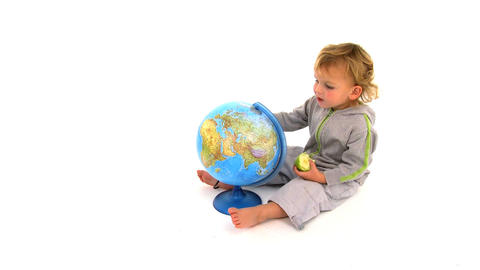 Cute toodler playing with a globe isolated on white Footage