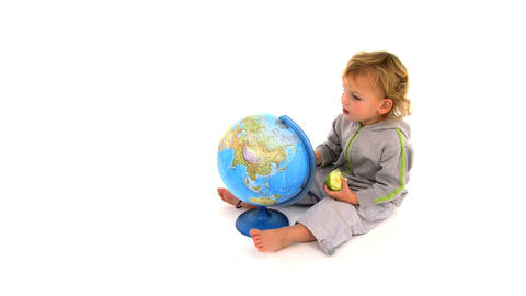 Cute toodler playing with a globe isolated on white Stock Video Footage