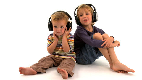 Two little boys listening to music on white background Footage