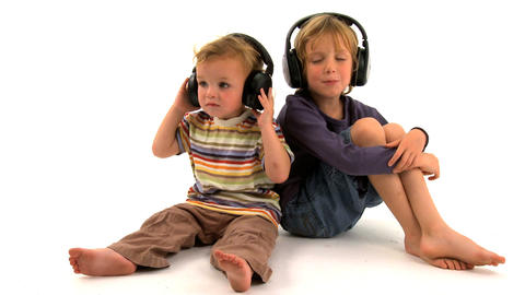 Two little boys listening to music on white background Stock Video Footage