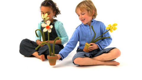 African american girl and blonde boy smelling at the flowers Footage