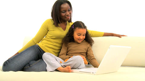 African american mother and her little daughter using a laptop Footage