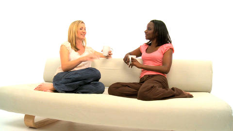 Attractive blonde and african american women talking on white background Footage