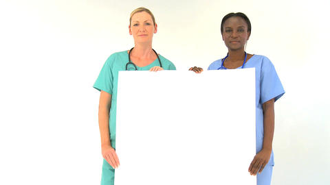 Female medical team holding blank notice-board isolated on white Footage