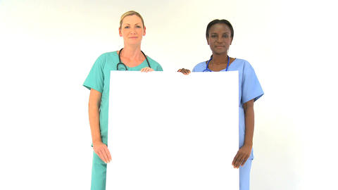 Female medical team holding blank notice-board isolated... Stock Video Footage