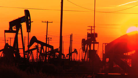Oil donkeys or pump jacks in perpetual motion at sunset Stock Video Footage