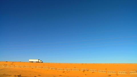 Highway trucks on a desert landscape Stock Video Footage