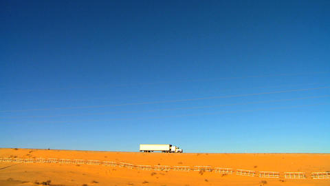 Highway trucks on a desert landscape Stock Video Footage
