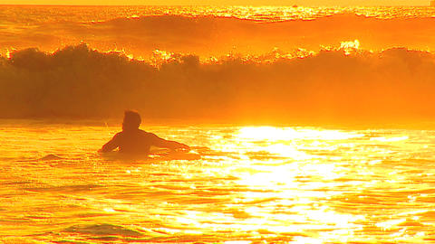 Surfer in the waves at sunset Stock Video Footage