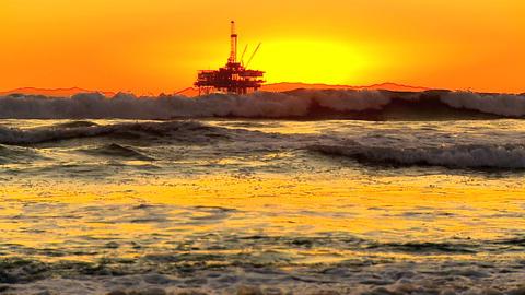 Oil platform & surfer waves at sunset Stock Video Footage
