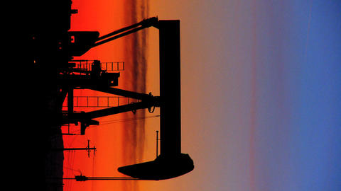 Vertical oil donkeys or pump jacks in perpetual motion at sunset Footage