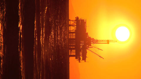 Vertical sunset over oil platform at sea Footage