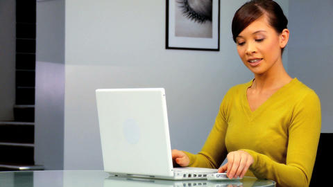 Young western oriental businesswoman using a laptop & mobile phone Footage