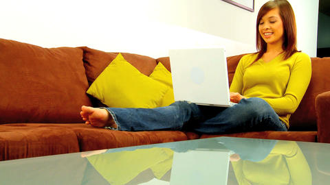 Young western oriental girl relaxing at home while using her laptop computer Footage