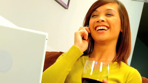 Young western oriental girl relaxing at home with her phone & a glass of wine Footage