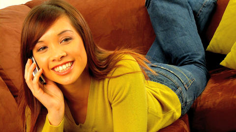 Young western oriental girl relaxing on her sofa & talking on a mobile phone Footage