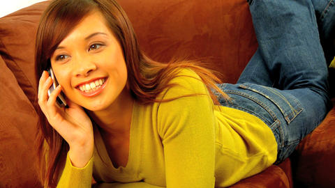 Young western oriental girl relaxing on her sofa &... Stock Video Footage