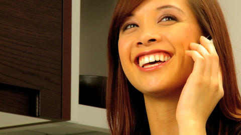 Young western oriental girl at home talking on her mobile... Stock Video Footage