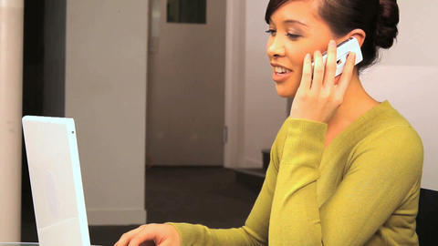 Young western oriental businesswoman taking a call at work Stock Video Footage