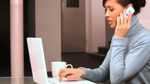 Young western oriental business woman taking a call at work Stock Video Footage