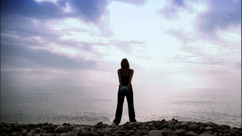 Young slim girl exercising on the beach at sunrise Stock Video Footage