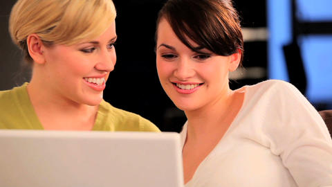Pretty friends having fun using a laptop computer Stock Video Footage
