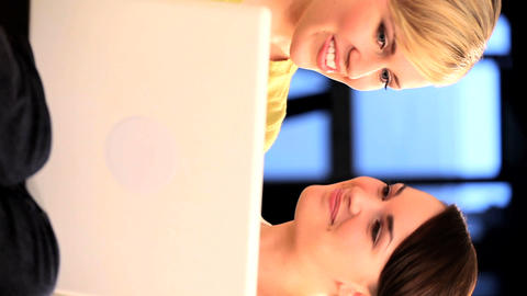 Vertical shot of pretty friends having fun using a laptop... Stock Video Footage