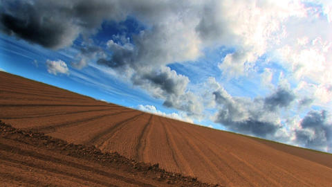 Dramatic time-lapse clouds over a ploughed field Footage