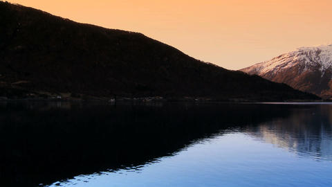 Sunrise over the crystal waters of a glacial fjord Stock Video Footage