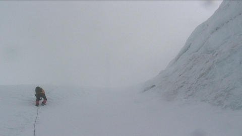 Climber, climbing past large ice wall Stock Video Footage