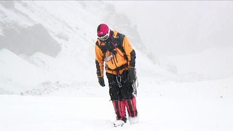 Climber approaching through falling snow Stock Video Footage