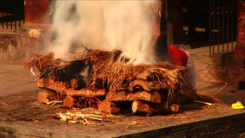 Man stoking large ceremonial fire Stock Video Footage