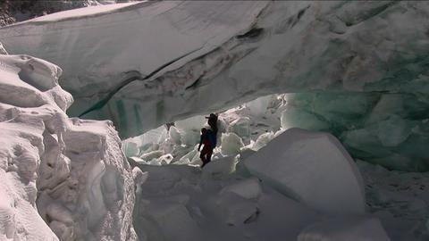 Climbers navigate under larger serac Stock Video Footage