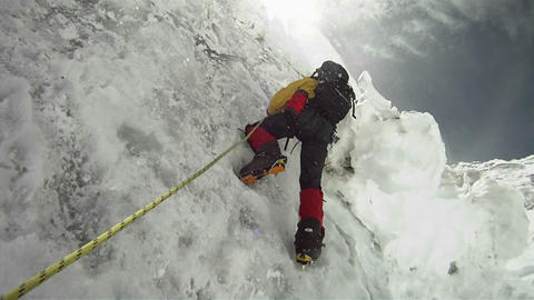 Climber on icy wall with wind and snow blowing Stock Video Footage