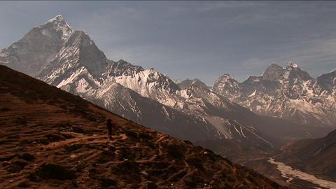 Trekker headed down trail peaks in background Stock Video Footage