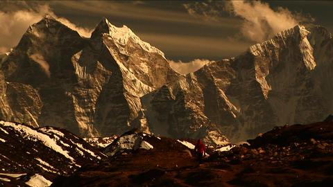 Trekker walking towards mountains Stock Video Footage